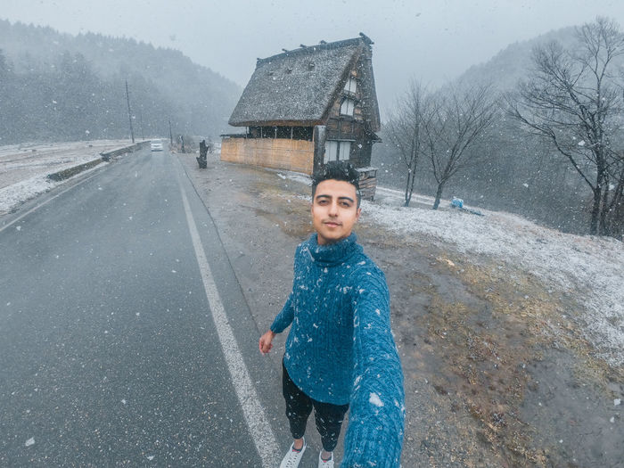 Portrait of smiling man on road during winter