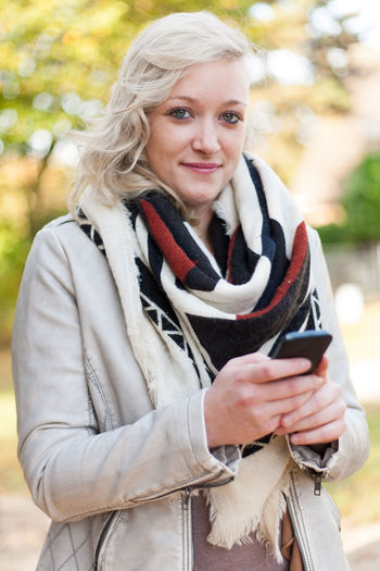 Attractive young woman using smart phone Autumnal Colours Autumnal Leaves Autumnal Mood Casual Clothing Caucasian Cell Phone  Communication Fall Colors Fall Season Mobile Phone Outside Person Smart Phone Smartphone Text Message Text Messaging Young Adult Young Woman