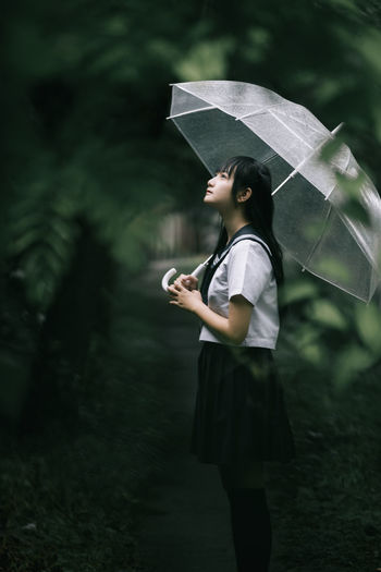 Side view of woman holding umbrella while standing in forest during rainy season