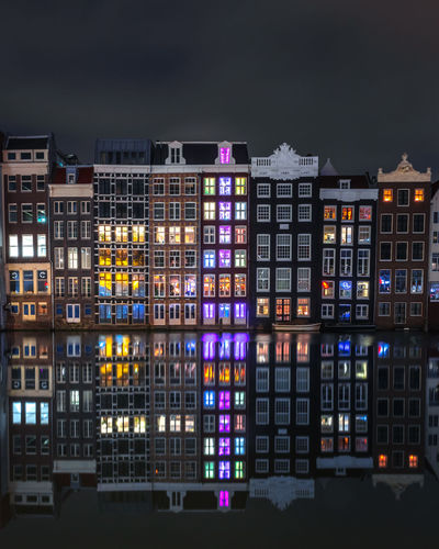 A very calm night in amsterdam with smooth reflections of the buildings on the water.