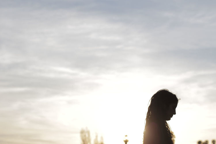 Side view of woman against cloudy sky during sunset