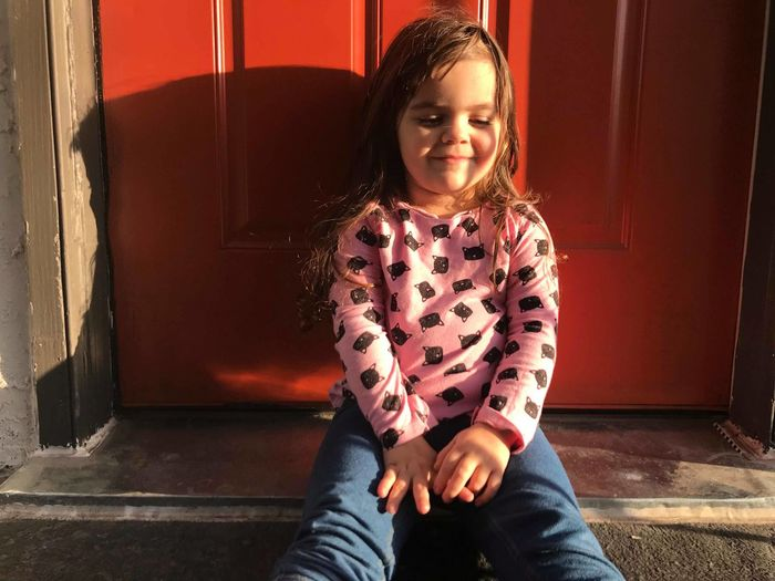 Girl smiling while sitting against closed red door