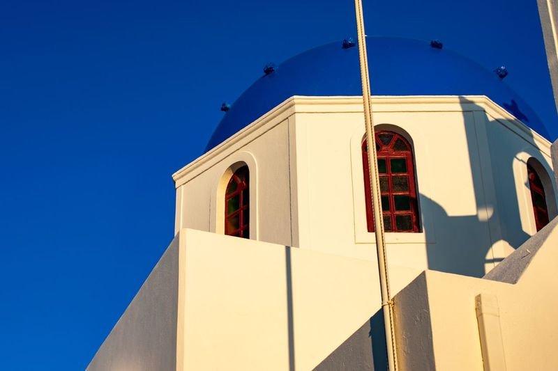 Church in Santorini Church Christianity Eyemphotography EyEmNewHere Summer Architecture Building Exterior Built Structure Blue Sunlight Low Angle View Sky Nature Building Clear Sky No People Day Shadow Window Religion Spirituality Belief Flag Sunny Outdoors