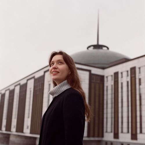 Side view of young woman standing against building