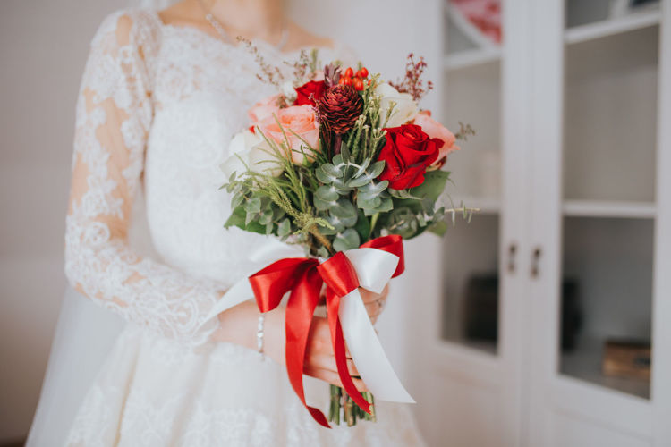 Red rose bouquet against white wall