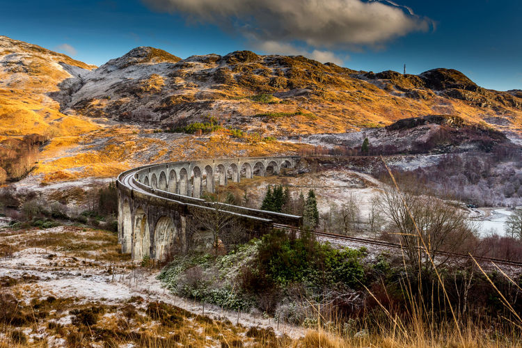 Glenfinnan Viaduct winters dawn in the Scottish Highlands Beauty In Nature Bridge - Man Made Structure Cloud - Sky Connection Day Harry Potter Highlands Landscape Mountain Mountain Range Nature No People Outdoors Scenics Scotland Sky Tranquility Transportation Tree Viaduct Water