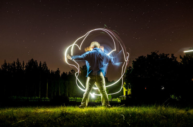 Boy doing light painting at night