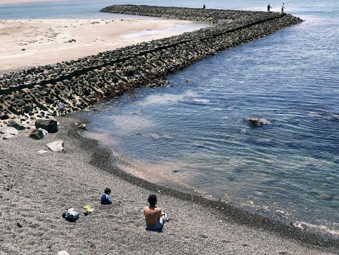 Beach Beauty In Nature Day Groyne High Angle View Land Leisure Activity Lifestyles Men Nature Outdoors People Real People Rock Sand Sea Sitting Solid Water