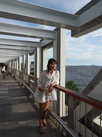 Full length of woman standing on railing against sea