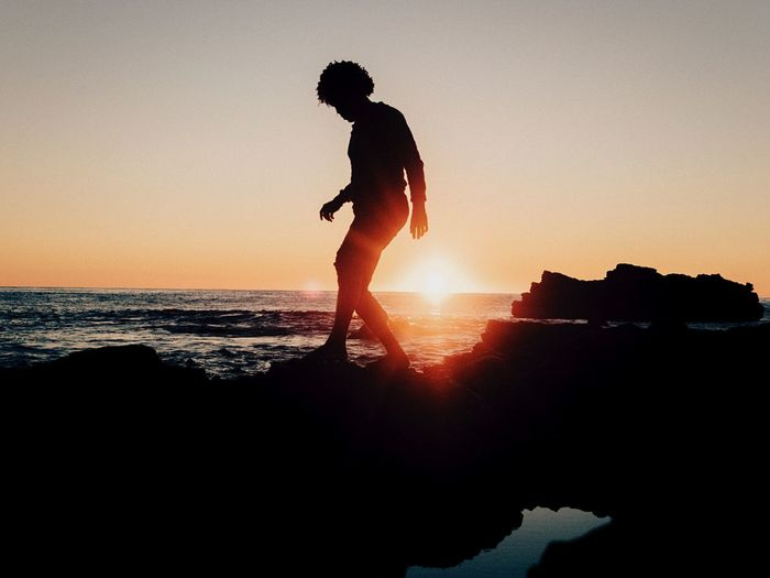 Silhouette person on rock formation by sea against clear sky during sunset