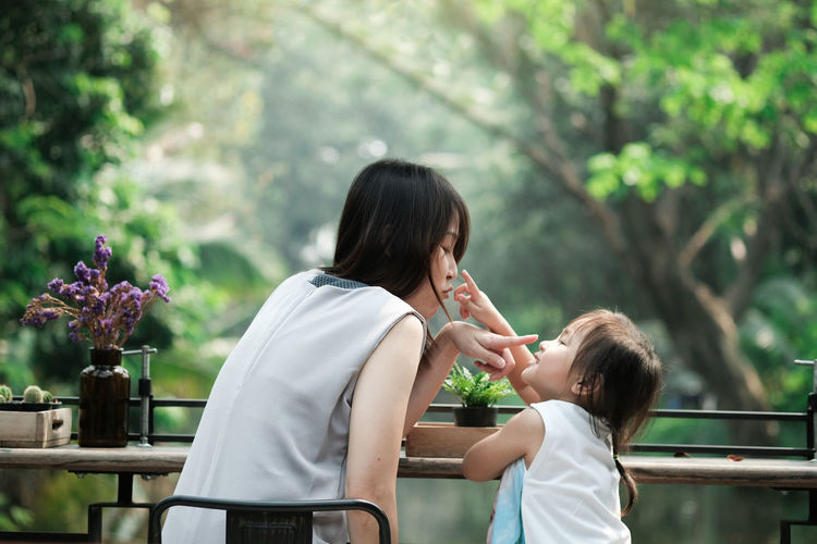 Mother and daughter talking, teaching, pointing, looking each other with beautiful river and tree background, Vacation time in a park with family. Adult Bonding Child Childhood Daughter Emotion Family Family With One Child Females Flower Flowering Plant Hairstyle Lifestyles Mother Outdoors Parent Plant Positive Emotion Real People Side View Togetherness Women