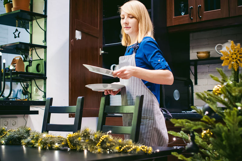 Woman Arranging Plates On Dining Table At Home During Christmas