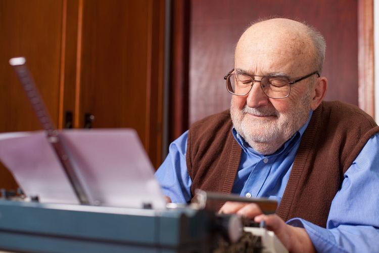 Senior Man With Typewriter Against Wall