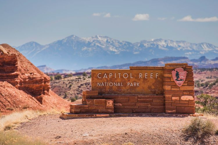 Capitol Reef National Park Entrance Sign. Utah, United States. Utah Capitol Reef National Park Sandstone Landscape Scenery Sign Sings Mountain Mountain Range Sky Environment Scenics - Nature Nature Non-urban Scene Text Day Communication Beauty In Nature No People Rock Land Tranquility Rock Formation Tranquil Scene Cloud - Sky Rock - Object Outdoors Formation Arid Climate Climate