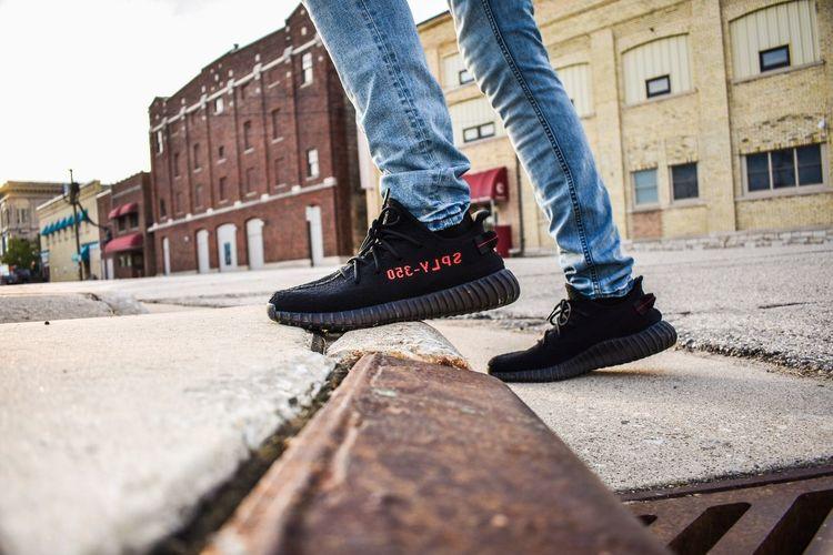Yeezy black and red Low Section Human Body Part Outdoors Building Exterior Street Human Leg Shoe Casual Clothing One Person Built Structure Day Architecture City People Lifestyles Adult Close-up Adults Only One Man Only Young Adult