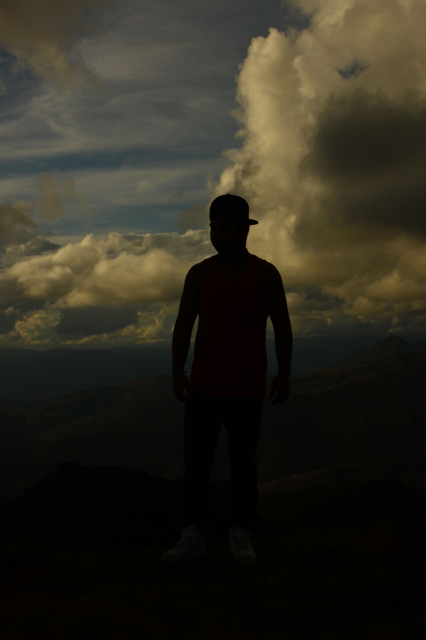 sky, silhouette, lifestyles, rear view, men, cloud - sky, standing, leisure activity, full length, mountain, cloudy, tranquility, tranquil scene, scenics, dusk, nature, beauty in nature, sunset