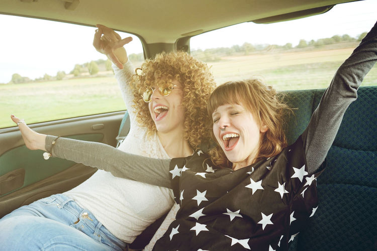 Cheerful Female Friends Sitting In Car