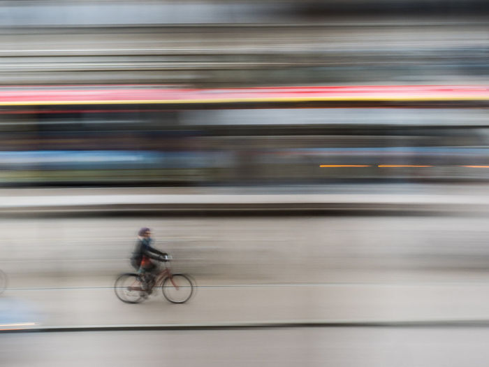 Blurred Motion Of Man Cycling On Bicycle In City