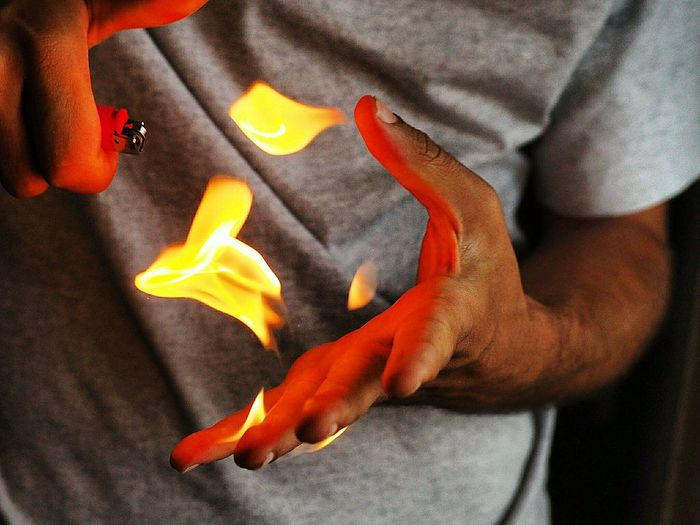 Midsection Of Man Playing With Flames