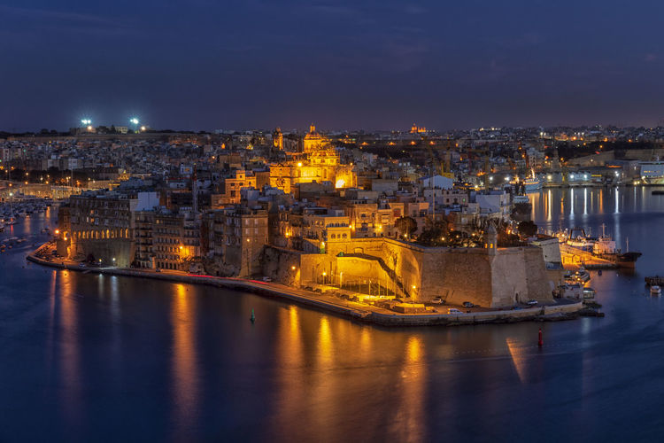 Illuminated buildings in city by sea at night