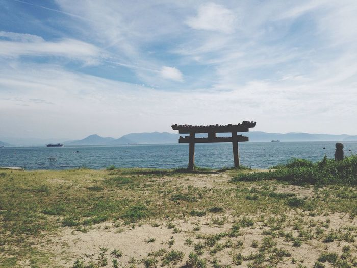 Abandoned torii gate on field by sea against sky