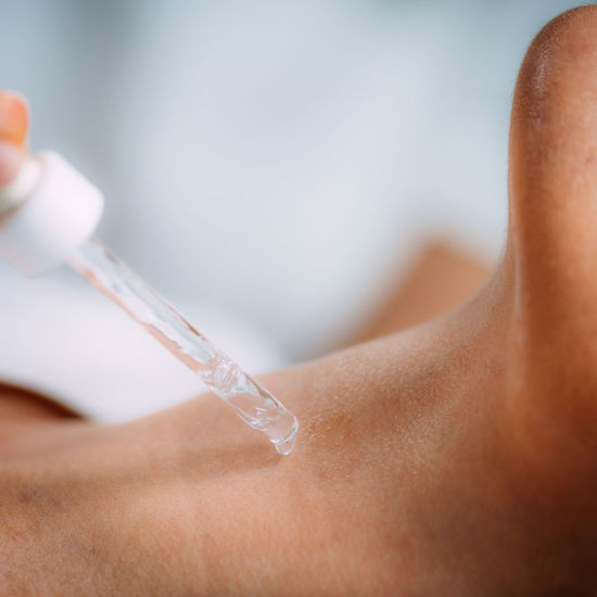 Neck anti-aging treatment. cosmetician applying hyaluronic acid serum on womans neck