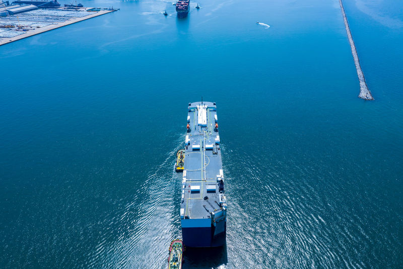 Aerial view ro-ro ship loading new cars. automotive container carriers sailing on the sea export