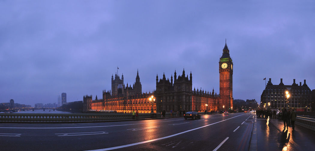 Illuminated Big Ben By Road Against Cloudy Sky At Dusk