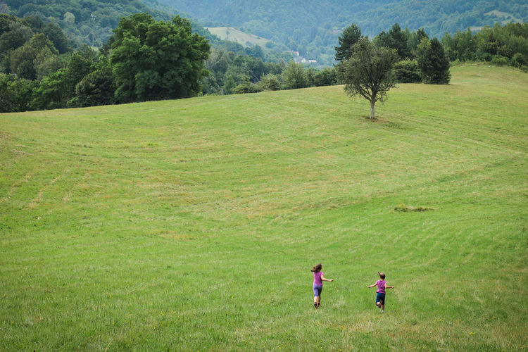 Rear View Of Sisters Running On Grassy Field