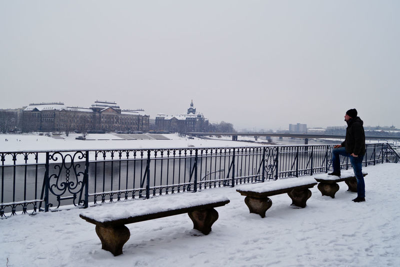 Man Standing On Snow Covered Footpath By River