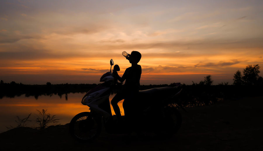 Silhouette boy drinking water while sitting on motor scooter against sky during sunset