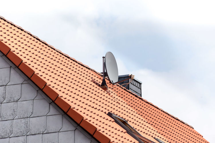 Satellite dish on a red tile roof