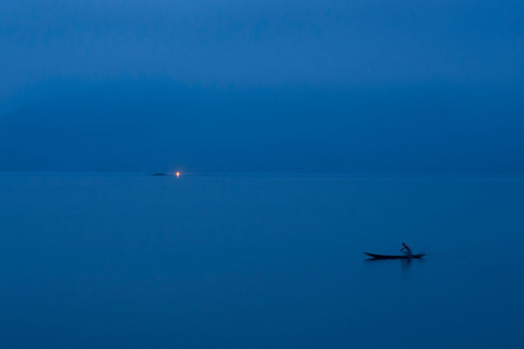 Person Sailing Boat In Lake Against Sky At Dawn