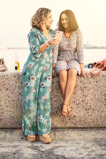 Two mid aged beautiful women talking while they're using a smartphone on the seaside. Two People Togetherness Women Bonding Smiling Emotion Hairstyle Positive Emotion People Love Young Adult Standing Water Full Length Leisure Activity Happiness Casual Clothing Young Women Real People Adult Day Hair Floral Pattern Adult Mid Adult Mid Age Outdoors Portrait Harbor View Seaside Seascape 40s Sun Friends Friendship Summer Sunset Colors Dressing Up Sitting Using Smartphone Smartphonephotography Cellphone Cheerleading Talking Sea