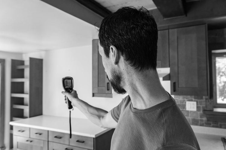 Portrait of young man holding camera at home