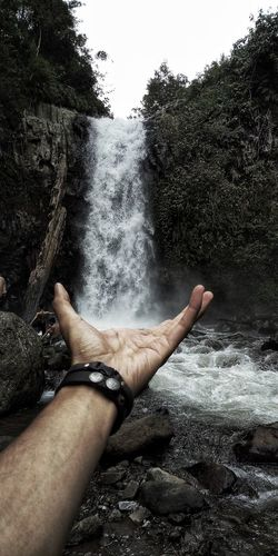 Cropped Hand Of Man Gesturing Towards Waterfall