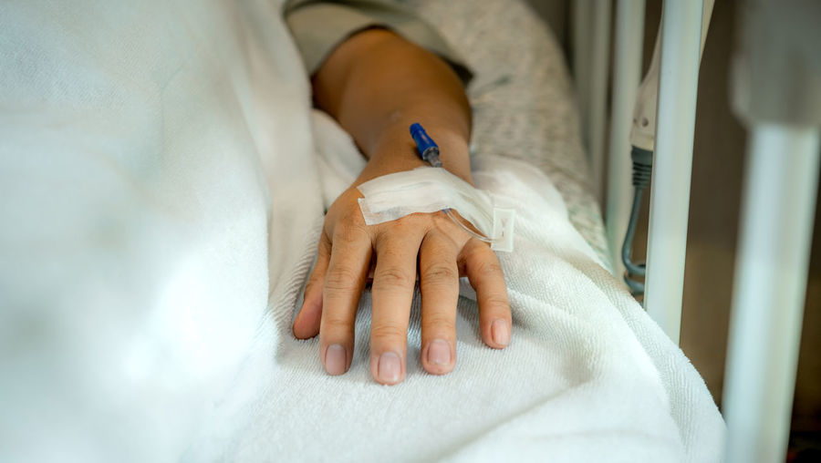 Close-up of woman holding hands on bed