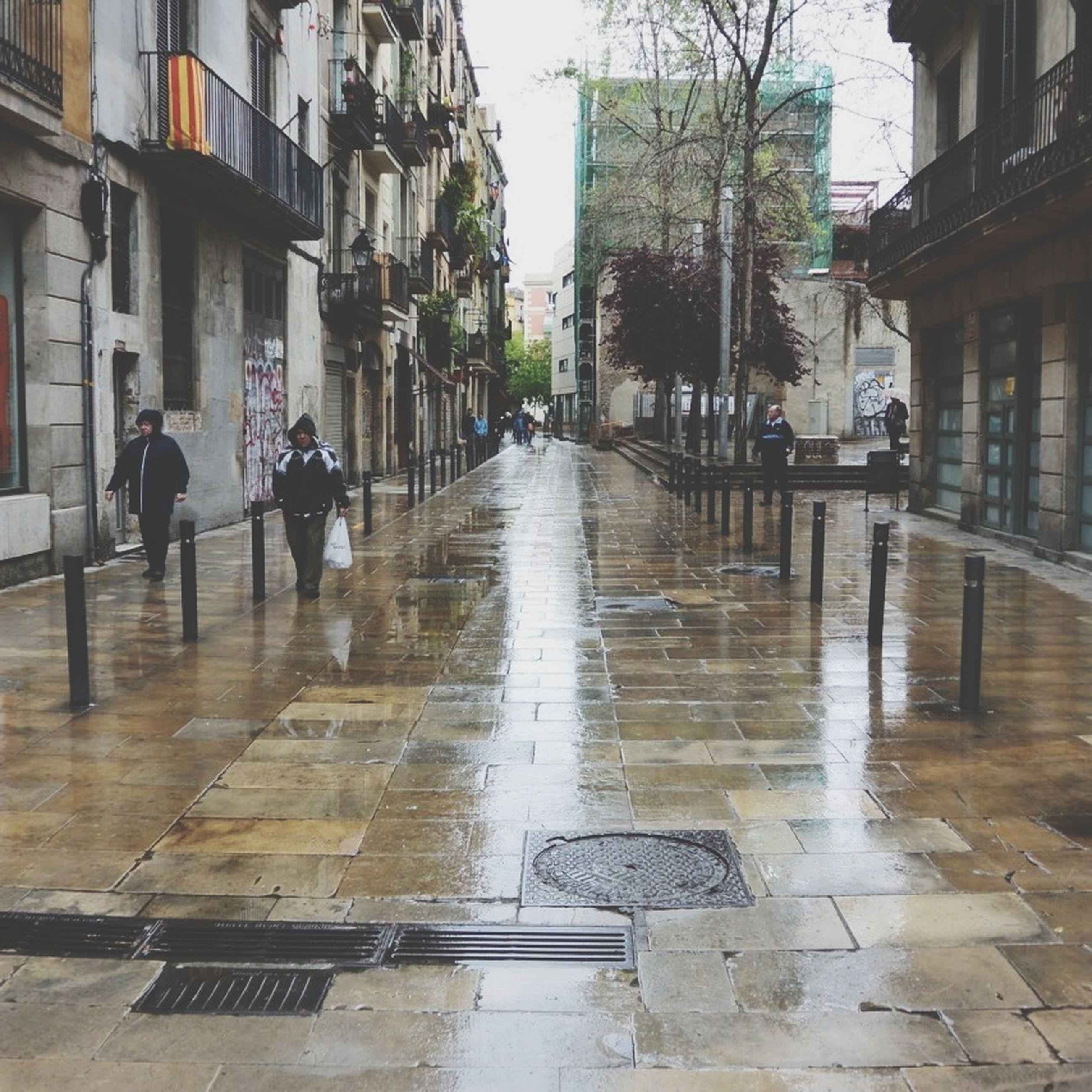 building exterior, architecture, built structure, street, city, wet, walking, city life, rain, transportation, men, incidental people, building, the way forward, reflection, sidewalk, person, city street, lifestyles