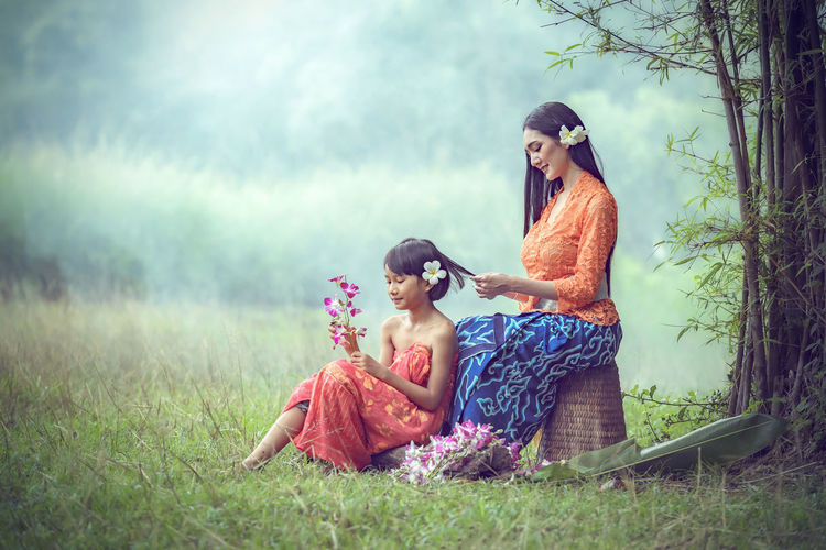 Smiling Mother And Daughter With Flowers Sitting On Field