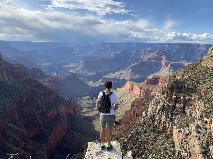Full length of man standing on cliff against canyon