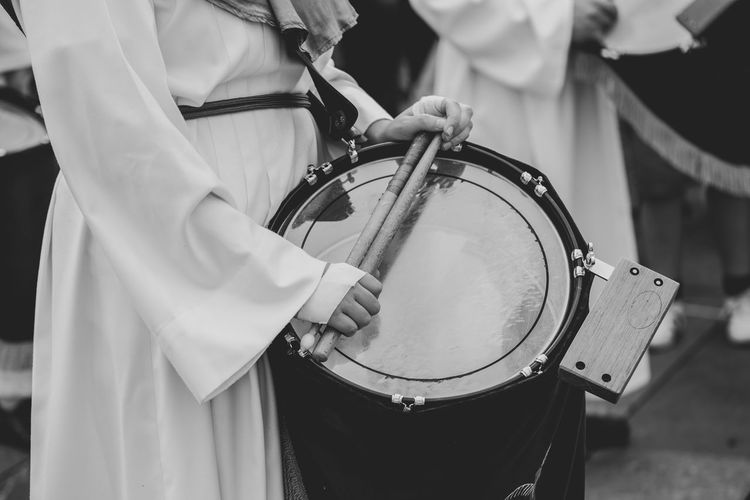 Midsection of person playing drum at parade