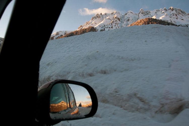Snow covered car on mountain against sky
