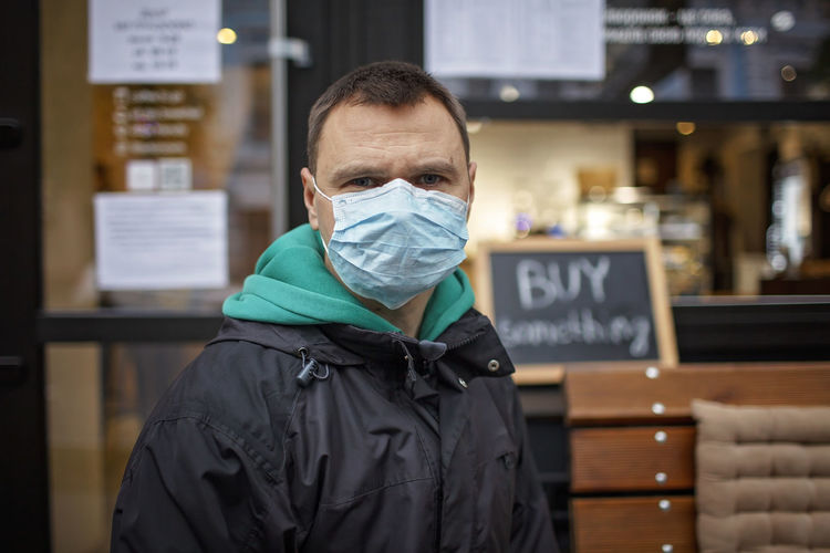 Portrait of man wearing mask standing in cafe