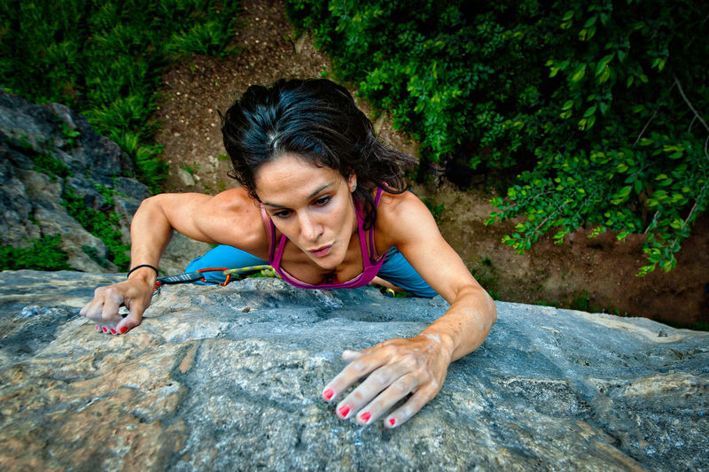 High angle view of woman climbing on rock
