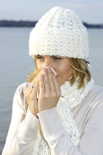 Woman with cold snuffs into a tissue Autumn Catched A Cold Tissue Walk Winter Woman Beauty Best Age Blond Hair Close-up Cold Day Headshot Lake One Person Outdoors People Portrait Sick Snuffs Warm Clothing Water Winter Young Adult Young Women