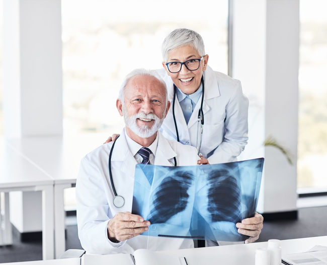 Portrait of smiling senior doctor holding medical x-ray by colleague in hospital