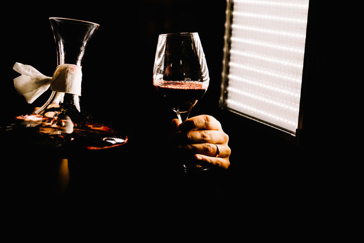 Hand holding wine glass against black background