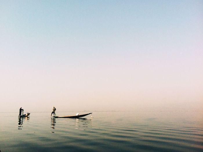 Fishermen in boat on lake against clear sky during sunrise