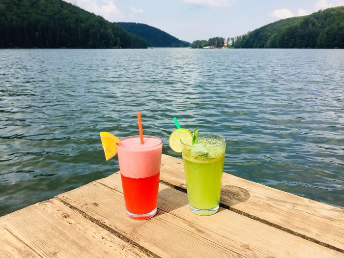 Strawberry lemonade and mint lemonade glasses with straws on wooden pontoon near the lake