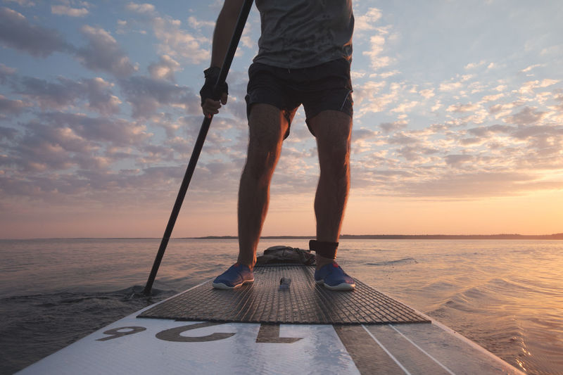 A man is rowing on a stand-up board. far from the coast. sunset sky in background